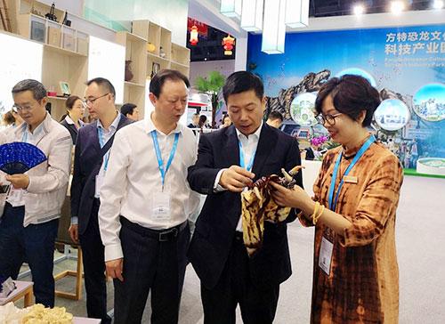 在西博会上总经理李娟向市委常委、副市长杨智艳介绍自贡天工扎染